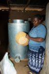 Esther Nduku, a maize farmer and trader in Embu, Kenya, shows her dry, clean maize grain, which she is storing in a metal silo. The silos can be made by local artisans using readily-available materials, take up little space, and enable farmers to store their grain without losses.   CIMMYT's Effective Grain Storage project, funded by the Swiss Agency for Development and Cooperation (SDC), is initially focusing on promoting these metal silos with partners in Kenya and Malawi, before widening the initiative to other African countries over a ten-year project. The silos were originally developed for Central America and have been adapted for Africa.   By providing a reliable means to store grain without loss of quality, the silos provide African farmers with a way to control their post-harvest losses. Rather than selling surplus grain straight away, they are able to wait and get a better price for their crop, stabilizing supplies and prices of maize while increasing farmers' food and income security.   Photo credit: CIMMYT.